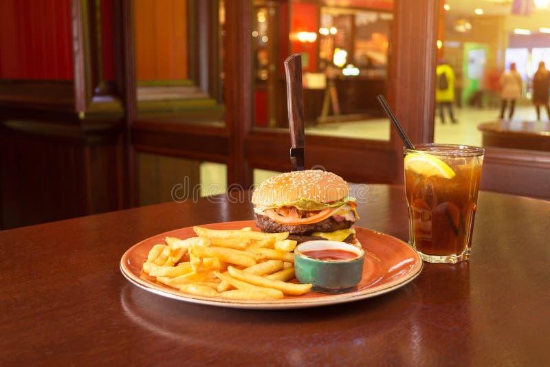 炸薯条和汉堡与刀子在中间乳酪在难看的东西板材,钢琴黏附了用番茄酱调味汁,与一杯公鸡 库存图片