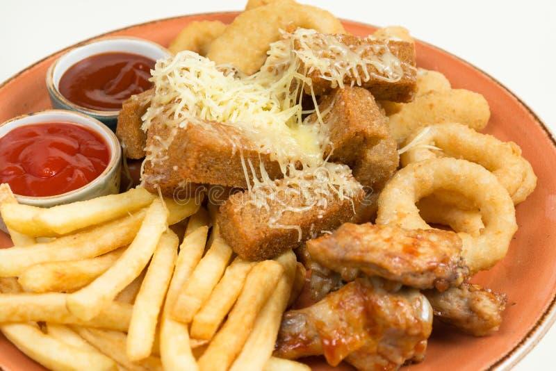 炸薯条,洋葱圈,鸡翼,面包干,对啤酒的一顿快餐在一块大板材用在棕色背景的两个调味汁 免版税图库摄影