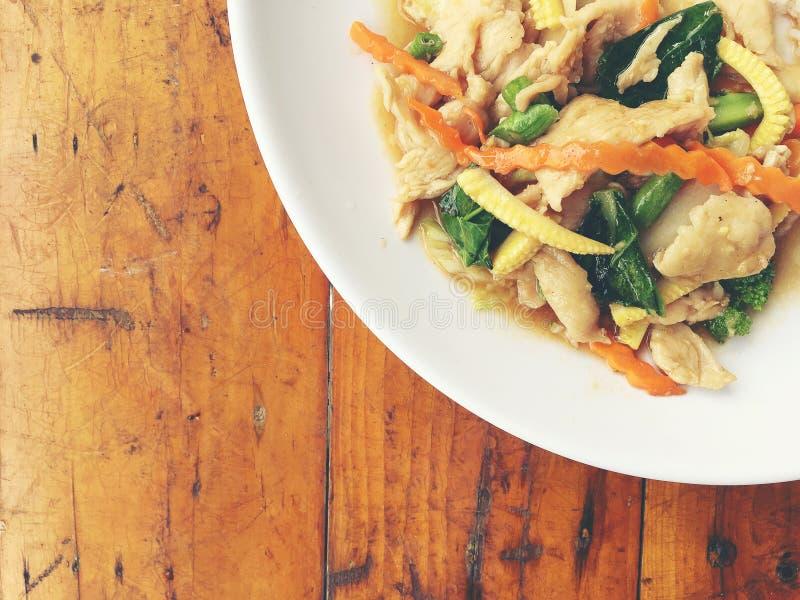 炸鸡混乱油炸物用米和中国菜用米和煎蛋在白色板材在木背景 菜为 免版税图库摄影