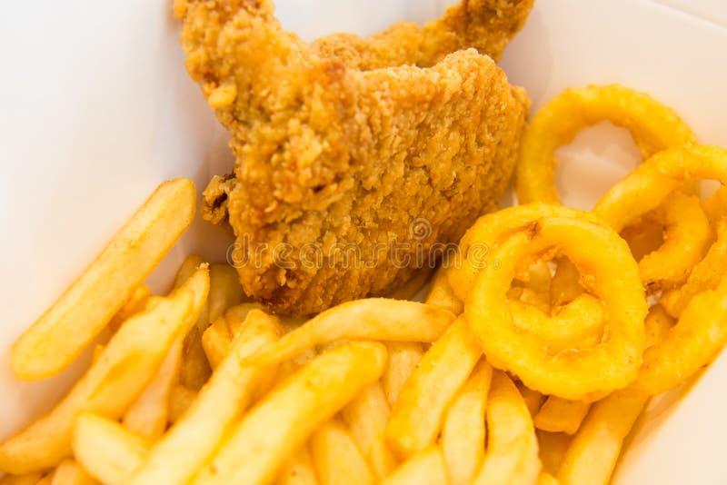 炸鸡用炸薯条和洋葱圈 免版税库存照片