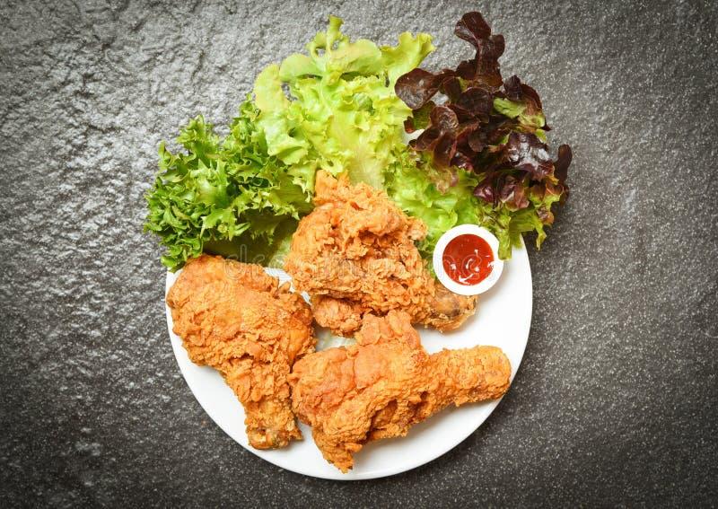 炸鸡白色板材的酥脆肯塔基有番茄酱和沙拉在黑暗的背景的莴苣菜的 免版税库存图片