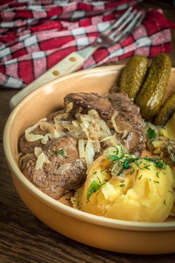 炸鸡肝脏用葱供食用土豆泥和酱瓜 库存图片