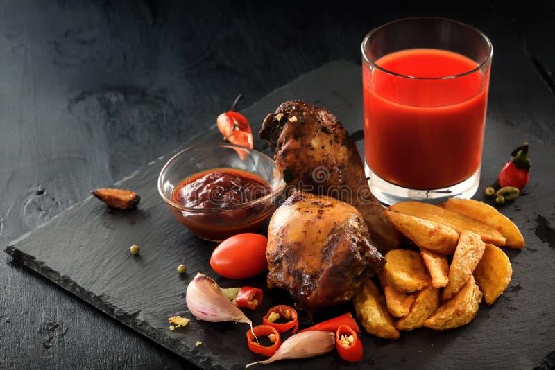 炸鸡腿用土豆、菜、蕃茄、胡椒、调味汁和一杯在黑背景的西红柿汁 图库摄影