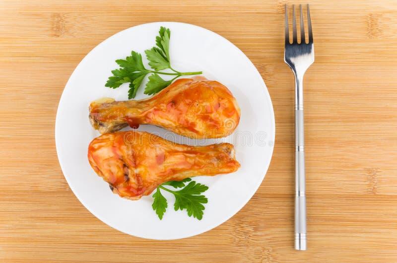炸鸡腿用西红柿酱和荷兰芹在板材 免版税库存图片