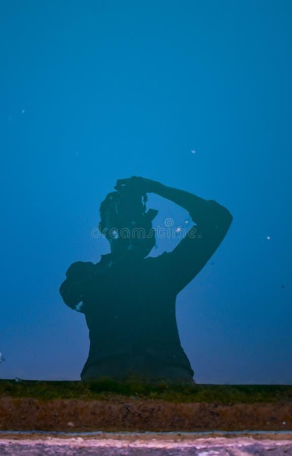 点击水的图片人/摄影师反射他的身体有天空蔚蓝背景 免版税库存照片