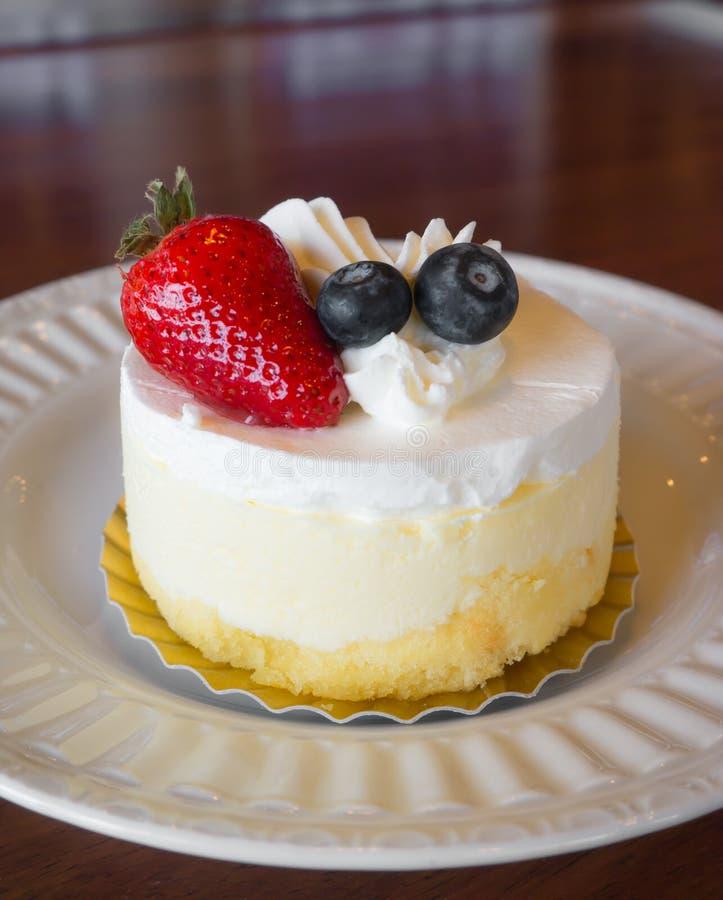 点心、甜白色奶油色蛋糕用草莓和莓果顶部 免版税库存图片