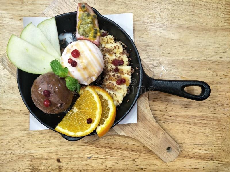 点心在木桌上的铁平底锅服务的冰淇凌 免版税图库摄影