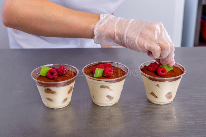 点心师在厨房做提拉米苏用莓 厨师在完成的点心上把巧克力放片断  ?? 免版税库存照片