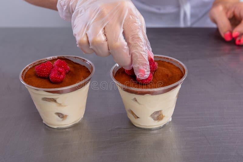 点心师在厨房做提拉米苏用莓 厨师在完成的点心上把莓放 在的主要类 免版税库存照片