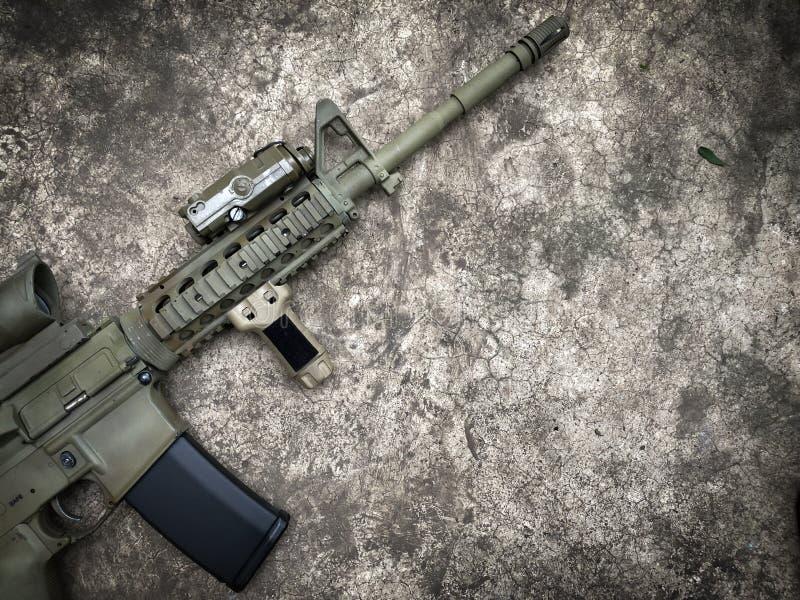点心攻击步枪在地面上的airsoft枪 库存照片