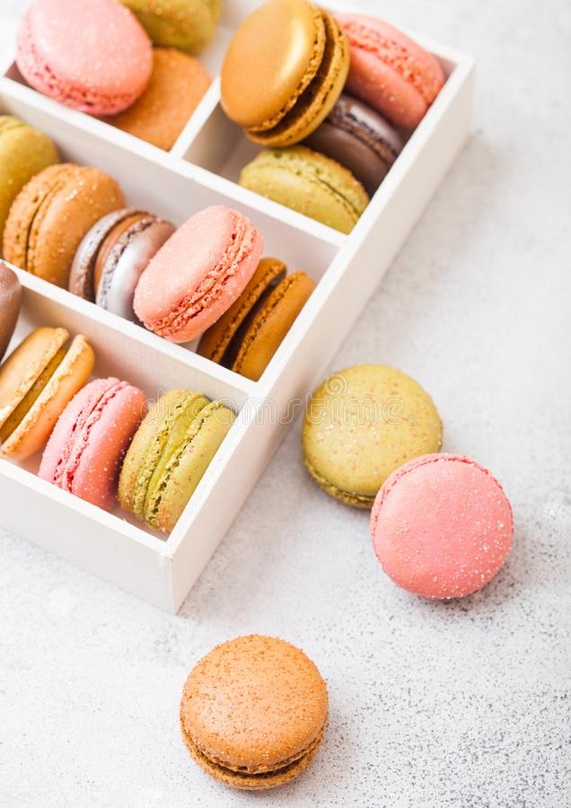 点心蛋糕macaron或蛋白杏仁饼干在白色木箱在石厨房用桌背景 顶视图 免版税图库摄影
