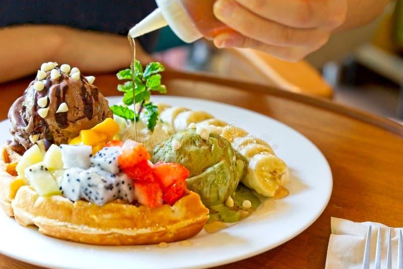 点心,奶蛋烘饼服务用混杂的果子、切的香蕉、巧克力冰淇凌和绿茶冰淇凌 免版税图库摄影