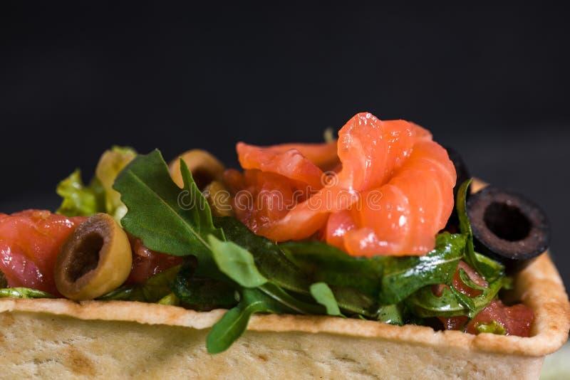 点心,红色鱼,沙拉开胃开胃菜在深黑色混凝土背景的一家餐馆 石盘子 免版税图库摄影