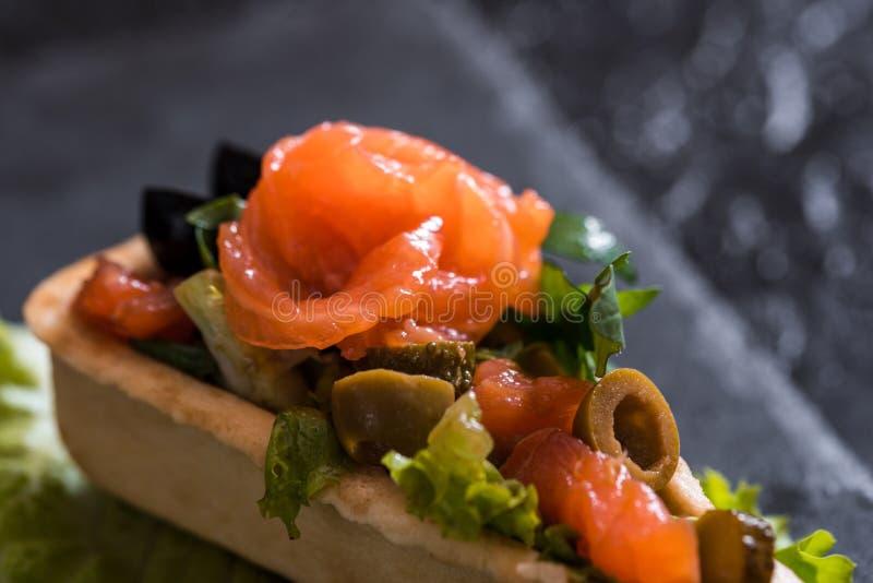 点心,红色鱼,沙拉开胃开胃菜在深黑色混凝土背景的一家餐馆 石盘子 库存图片