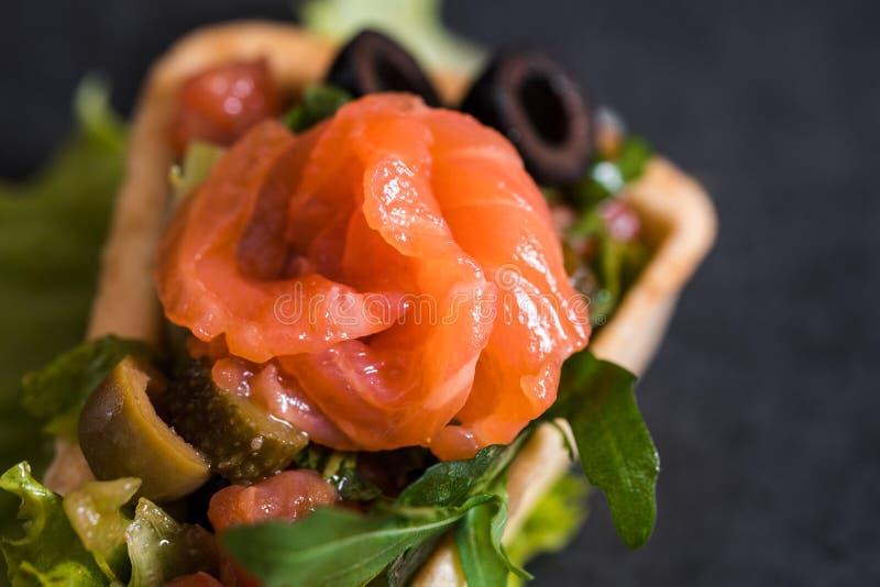 点心,红色鱼,沙拉开胃开胃菜在深黑色混凝土背景的一家餐馆 石盘子 免版税库存图片