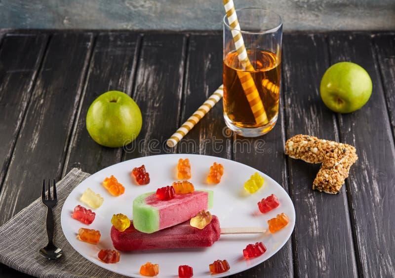 点心-在西瓜形式和口味的冰淇凌和与樱桃、甜点、苹果和一杯口味在a的汁液 库存图片