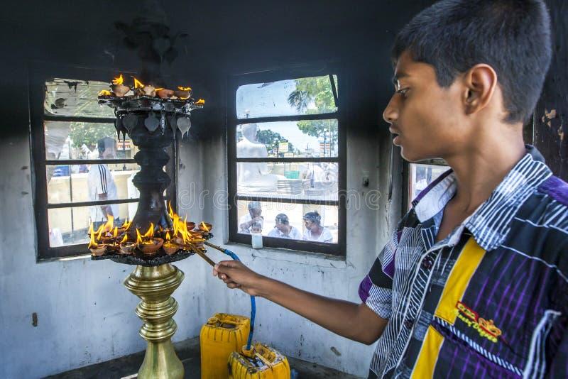 点燃一盏油灯在Nagadipa Vihara寺庙在Nainativu海岛的一个佛教崇拜者在斯里兰卡的贾夫纳地区 库存照片