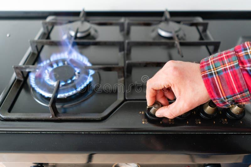 点燃与通过自动电燃烧的一个人气体火炉 现代煤气喷燃器和滚刀在厨灶 免版税图库摄影