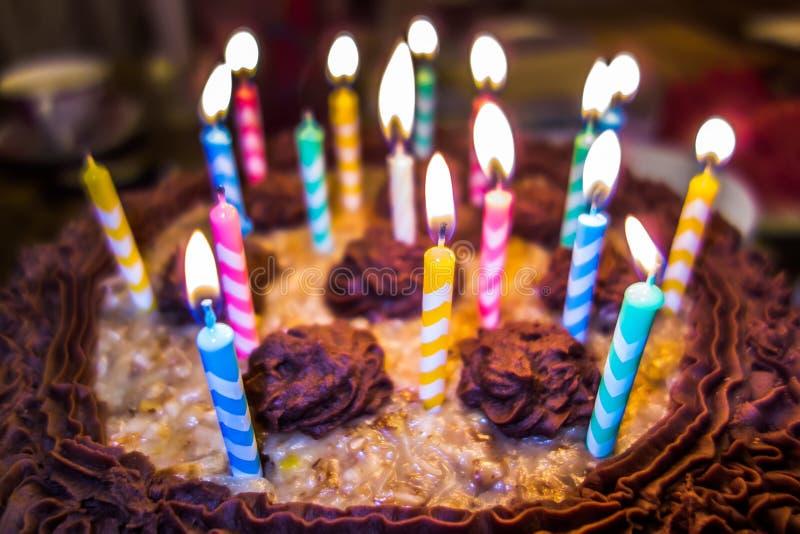 点燃在生日蛋糕的五颜六色的蜡烛 免版税库存图片
