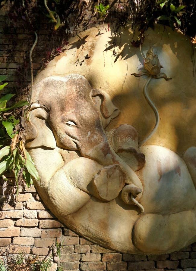 点燃在睡觉在墙壁上的大象雕塑 免版税库存图片