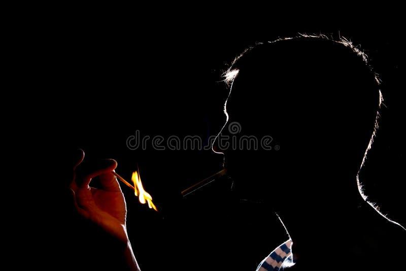 点燃在黑暗的香烟人的剪影  免版税库存图片
