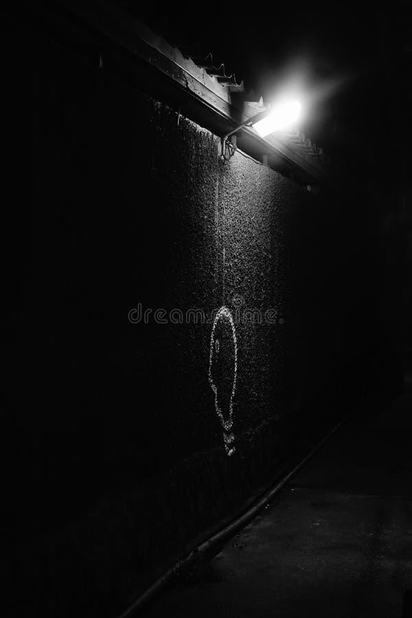 点燃在黑暗,在黑暗,电灯泡的灯被绘在墙壁的纹理,抽象背景概念 免版税库存照片