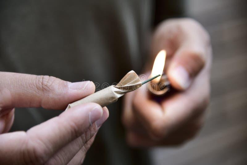 点燃爆竹的年轻人 免版税库存照片