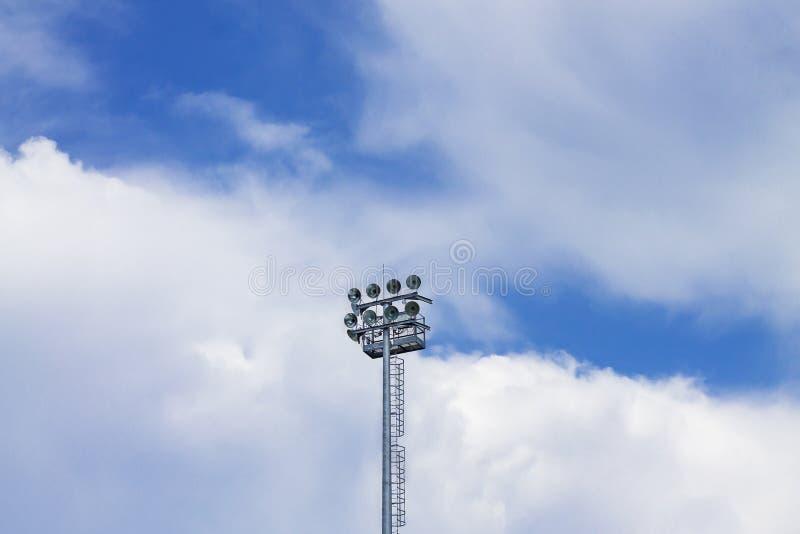 点燃聚光灯反对天空蔚蓝的体育体育场 免版税库存照片