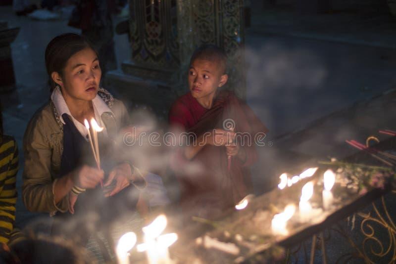 点燃蜡烛的新手修士和妇女在佛教寺庙 库存图片