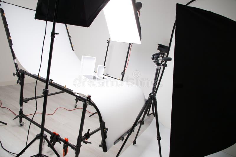 点燃设定在商业工作的演播室例如照片与大softbox snoot反射器伞和三脚架的对象产品 免版税库存照片