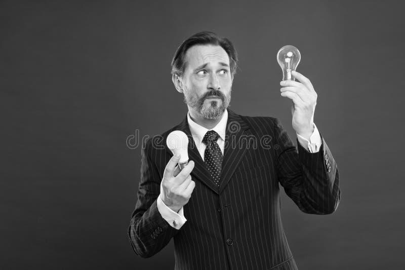 点燃选择存金钱 在红色背景的人有胡子的顾问正装举行电灯泡 想法的标志 免版税库存照片