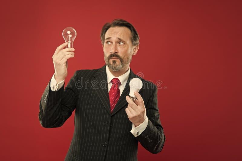点燃选择存金钱 在红色背景的人有胡子的顾问正装举行电灯泡 想法的标志 库存图片