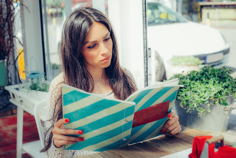 点美丽的妇女看菜单和食物在餐馆 免版税库存图片