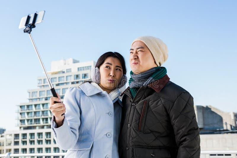 点击滑稽的图片的夫妇通过手机 免版税库存图片
