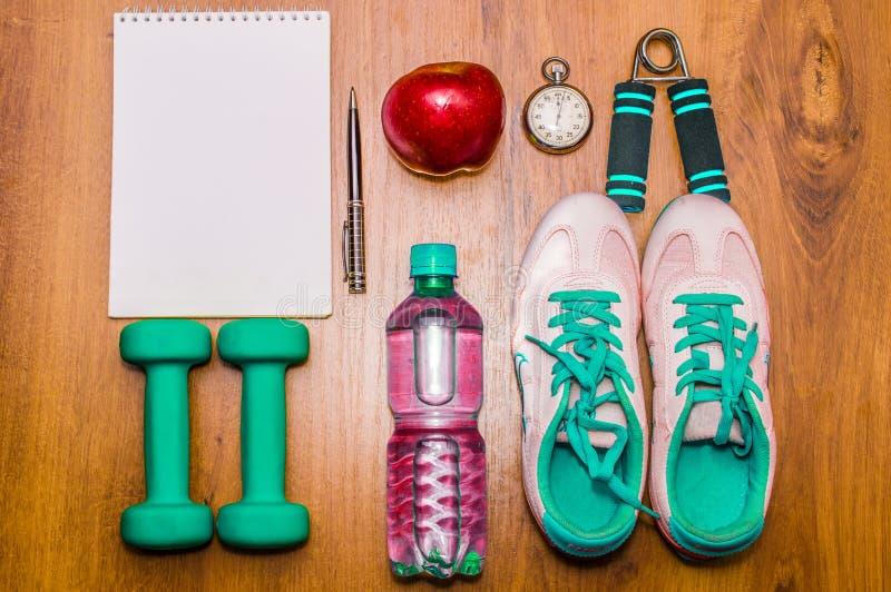 锻炼和健身节食的拷贝空间日志 概念健康生活方式 哑铃,水,扩展器在土气的手触球 库存图片