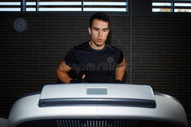 锻炼的英俊的深色的人在快速地跑在踏车的健身房 图库摄影