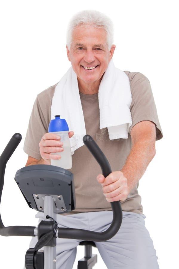 锻炼脚踏车的老人 免版税库存图片