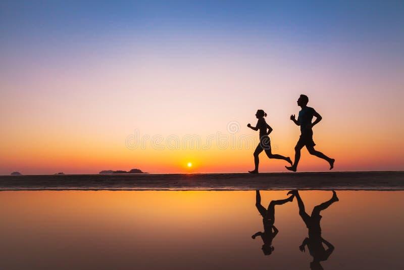 锻炼,两个赛跑者剪影在海滩的 免版税库存照片