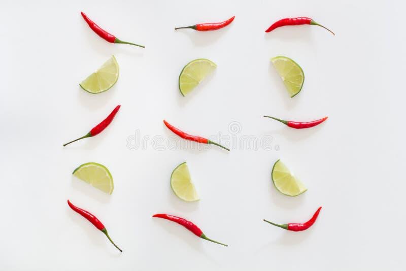 炽热辣椒和被切的石灰的样式在白色背景 免版税图库摄影