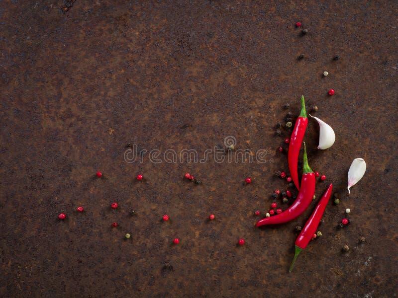 炽热辣椒荚和豌豆,在黑暗的生锈的m的拨蒜 免版税库存图片