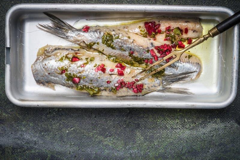 烂醉如泥的鲱鱼用在碗用卤汁和叉子的草本在土气背景,顶视图 免版税库存照片