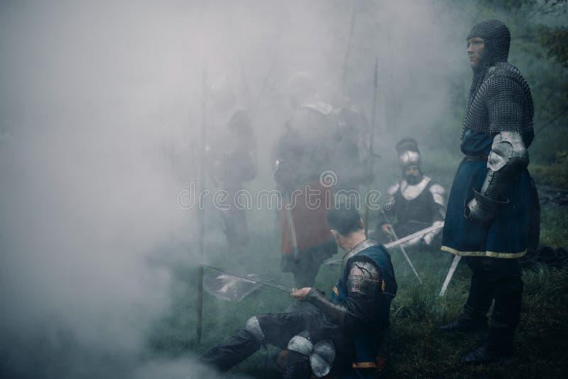 烈士的中世纪骑士争斗小队在一个有薄雾的森林里休息 免版税库存照片