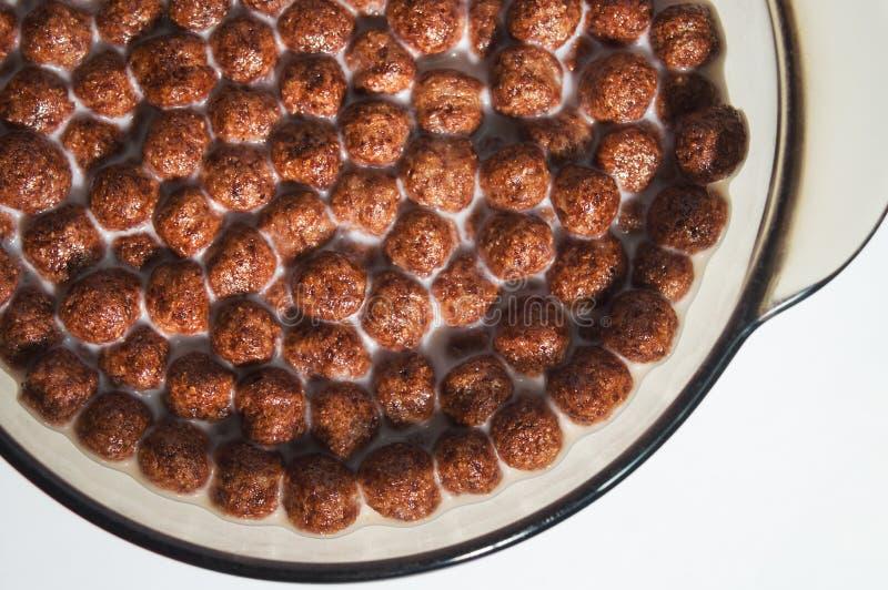 烘干健康巧克力早餐以在牛奶板材的球的形式  麦子和玉米剥落  免版税库存图片