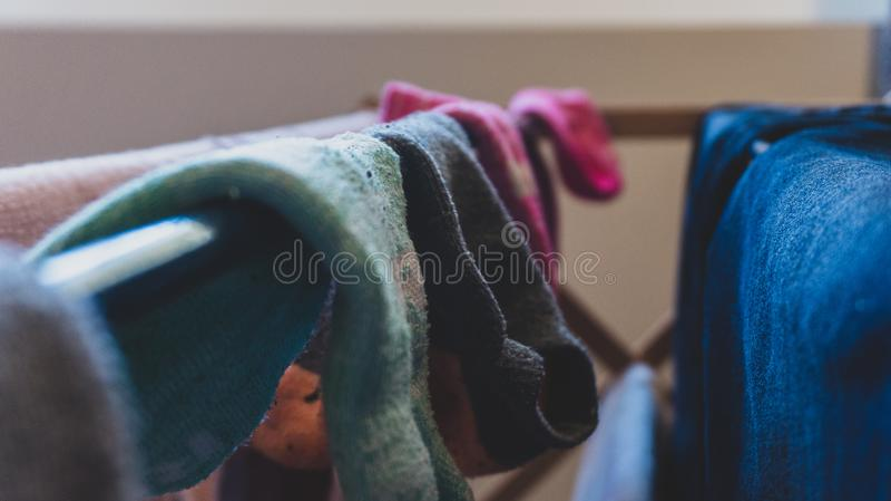 烘干在洗衣店机架的被配错的袜子对黑暗,被过滤的,退色的看法,垂悬在洗涤烘干,与蓝色牛仔裤以后 库存照片