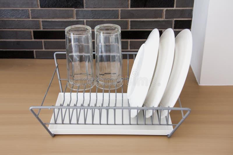 烘干在金属碗架的白色盘 免版税图库摄影