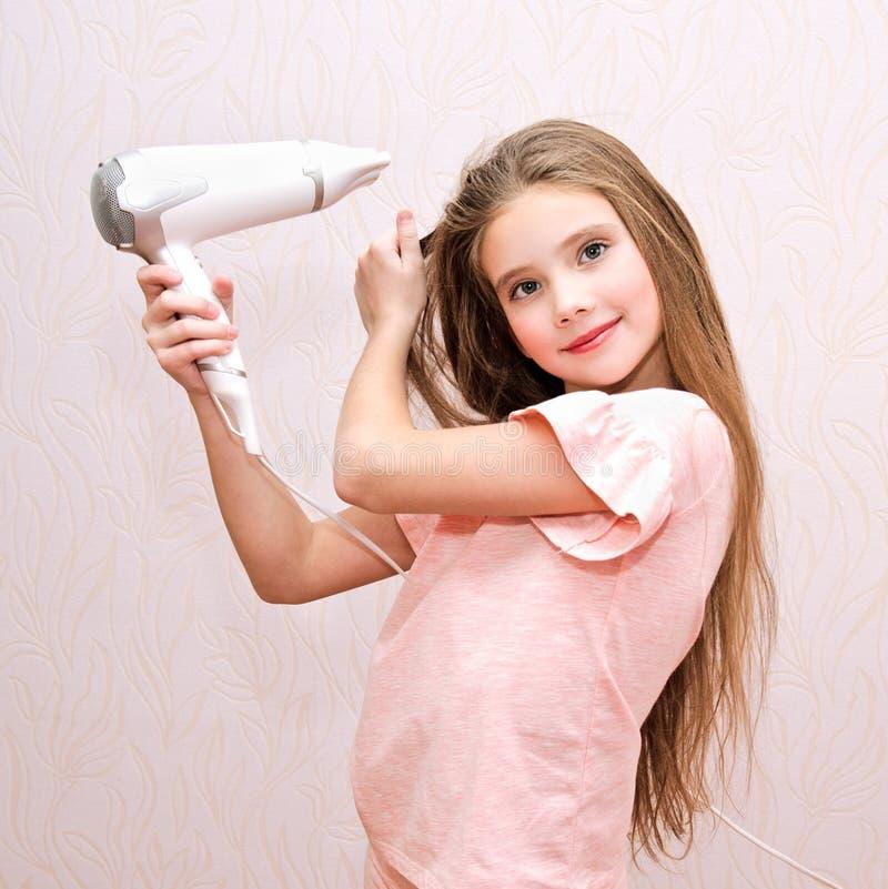 烘干她的有吹风器的逗人喜爱的微笑的女孩孩子长发 免版税图库摄影