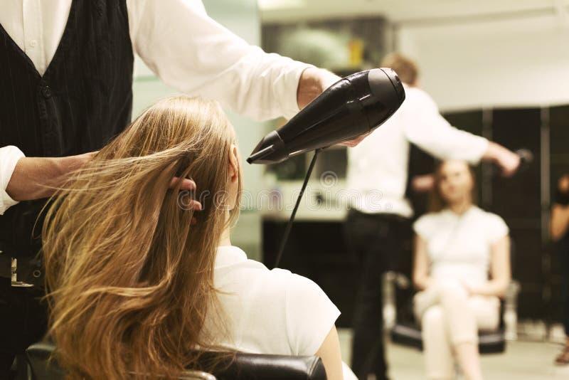 烘干有吹风器的美发师女孩的头发在发廊 免版税库存照片
