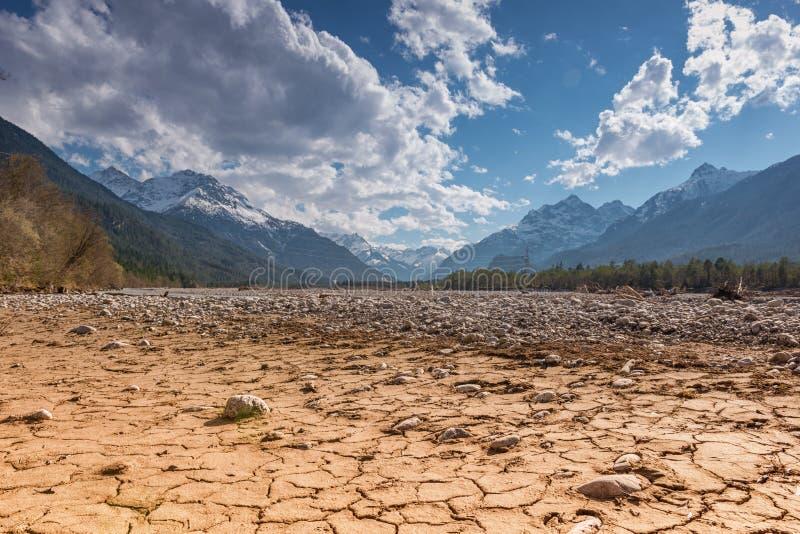 烘干破裂的河地球地面和蓝天 免版税库存图片