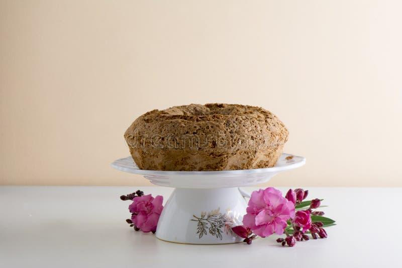 烘烤与糖粉桃红色花的圆环蛋糕 免版税库存照片
