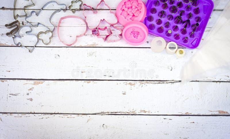 烘烤为曲奇饼和蛋糕模子的工具松饼和杯形蛋糕的在白色木背景 免版税库存照片